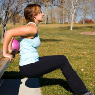 Young woman performing tricep dips on a bench.