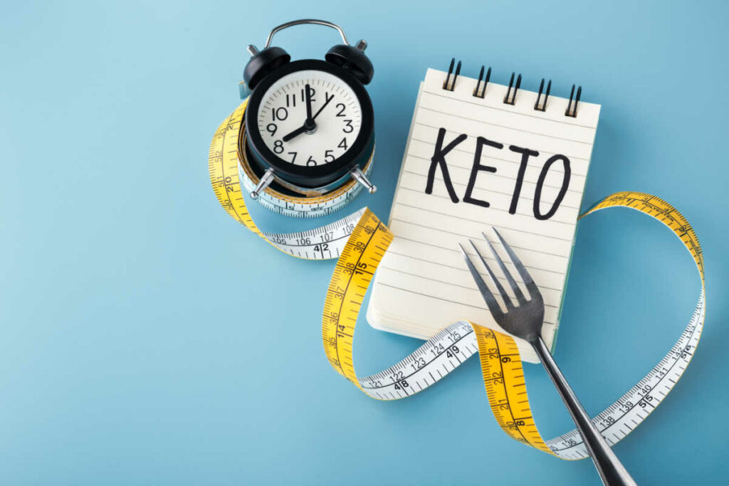 Intermittent Fasting On Keto clock fork and notepad